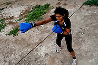 A Peruvian woman practices punching and movement while training in the outdoor boxing school at the Telmo Carbajo stadium in Callao, Peru, 4 April 2013.