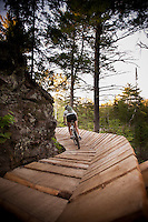 A female mountain biker rides a wooden boardwalk section of The Flow trail of Copper Harbor Michigan.