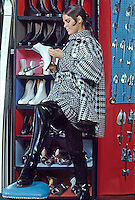Ali MacGraw models winter fashion and thigh-high vinyl boots at the Princeton Skate and Ski Shop, Princeton, New Jersey, 1967. Photo by John G. Zimmerman