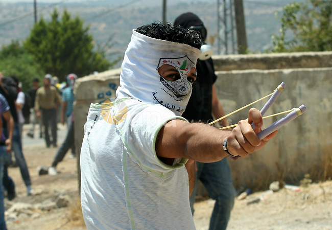 A Palestinian protestor throws stones during clashes with Israeli troops following a weekly protest against the Jewish settlement of Kdumim, near Nablus,in the northern West Bank village of Kufr Qaddum, June 29, 2012. Photo by Nedal Eshtayah