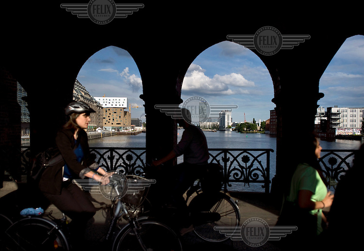 People cycle across the Oberbaumbruecke with a view towards the Mediaspree city project with the Universal building, Nhow-Hotel and the Treptowers at the Osthafen at the river Spree in Berlin Kreuzberg-Friedrichshain.