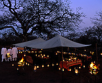 In the grounds of a country house hotel in Africa an outdoor dining room has been created under canvas and lit with storm lanterns in old-fashioned colonial safari-style