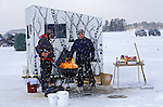 .Warming up on while waiting for the fish to bite during an ice fishing contest on Plum Lake in Vilas County in Northern Wisconsin.