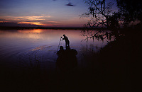 A boater push poles out into still waters of the St. Marys River at dusk. <br /> The St Marys River divides Florida and Georgia, flowing out of the Okefenokee Swamp to the Atlantic Ocean.