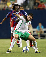 Costa Rica's Dennis Marshall (20) pressures Mexico's Guillermo Franco (10).  Mexico defeated Costa Rica 2-1 on penalty kicks in the semifinals of the Gold Cup at Soldier Field in Chicago, IL on July 23, 2009.