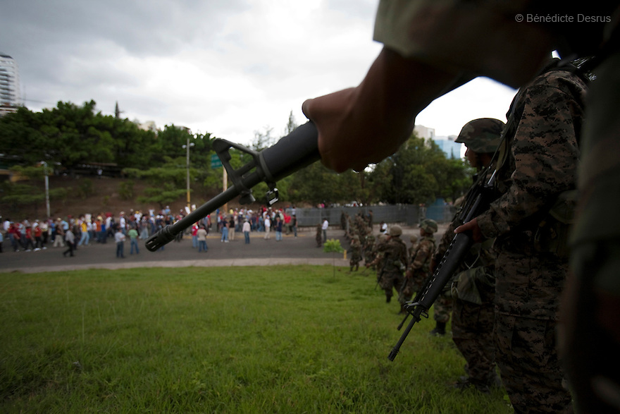 3 July 2009 - Tegucigalpa, Honduras  Soldiers stand guard as supporters of Honduras' ousted President Manuel Zelaya pass by during a march near the presidential palace in Tegucigalpa. Zelaya has been forced into exile after being arrested by a group of soldiers in an apparent military coup. Photo credit: Benedicte Desrus