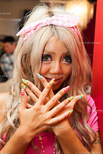 Harutamu, a member of staff, shows off her nail art at the Ganguro Cafe &amp; Bar in the Shibuya shopping area on September 4, 2015. <br /> <br /> Ganguro is an alternative Japanese fashion trend which started in the mid-1990s where young women, rebelling against the traditional idea of Japanese beauty, wore colorful make-up and clothes and had dark-skin.<br /> <br /> 10 Ganguro fashion girls work in the new bar, which offers original Ganguro Balls (fried takoyaki style sausage balls in black squid ink batter) on its menu. Ganguro Caf&eacute; &amp; Bar also offers special services such as Ganguro make-up and the chance to take purikura (photo booth pictures) with staff and to look like a Ganguro girl walking around the Shibuya streets.<br /> <br /> The bar is popular with both Japanese and foreigners and has menus translated in English. (Photo by Rodrigo Reyes Marin/AFLO)