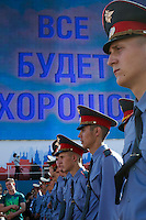 "Moscow, Russia, 12/06/2010..Police in Red Square stand under a giant display covering Lenin's mausoleum and reading ""Everything Will Be Alright"" at a concert to mark the Russia Day national holiday."