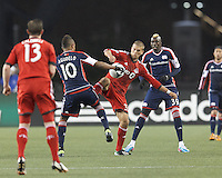 Toronto FC defender Ryan Richter (33) and New England Revolution midfielder Juan Agudelo (10) battle for the ball. In a Major League Soccer (MLS) match, the New England Revolution (blue) defeated Toronto FC (red), 2-0, at Gillette Stadium on May 25, 2013.
