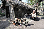 Pov Ean feeds her chickens in the Cambodian village of O Kroich, where residents are members of the Kouy indigenous group. Pov Ean participates in a rice bank sponsored by the Community Health and Agricultural Development program of the Methodist Mission in Cambodia.