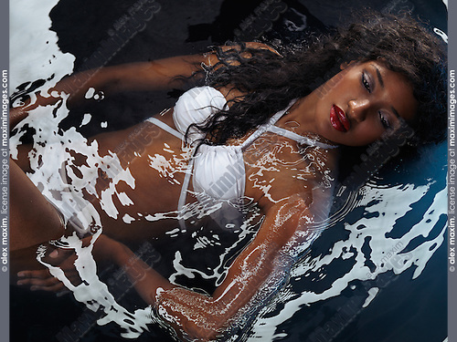 Beautiful black woman wearing a white swimsuit lying in shiny water
