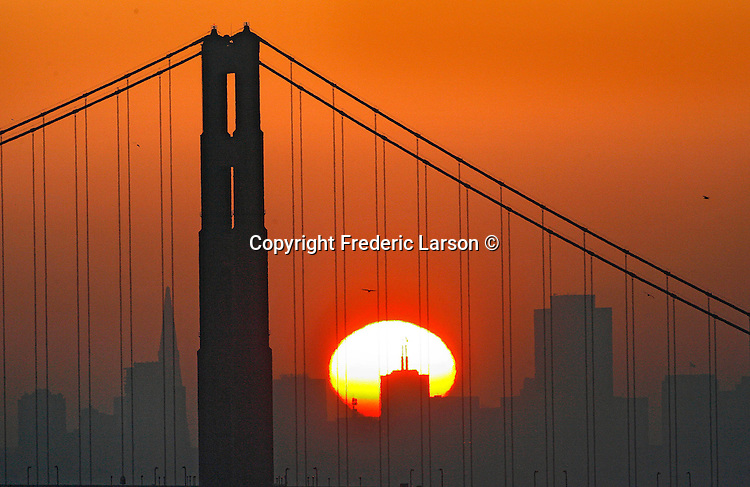 """Here comes the sun,"" through the Golden Gate Bridge between the tallest buildings from Point Bonita the sunrise pokes through the low lying haze blanketing the city skyline."