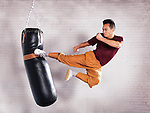 Martial artist, Shaolin Kung Fu instructor Shi Chang Dao practicing flying kick on a punching bag