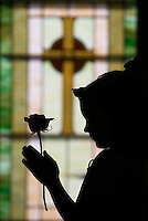 A young girl stands with a rose before a stained glass window after her first communion sacrament at a Catholic church in Johnstown, OH.<br />