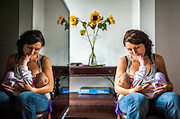 A young woman breastfeeds her baby in her living room at home. They are reflected in the television.<br /> <br /> 10/09/12<br /> Berkshire, England, UK