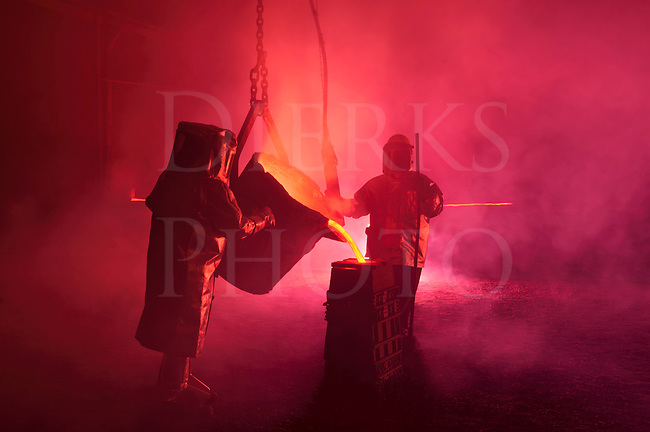 Pouring molten iron in a steel mill reenactment, metalurgical workers with ladle bucket, hot, smoky, and dangerous, Bethlehem, Pennsylvania, USA.