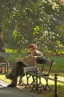 Poland, Krakow, Man reading newspaper on park bench