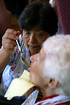 A woman with Alzheimer's disease is spoon fed by a healthcare worker  at  live-in residence for Alzheimer's and dementia related  patients.