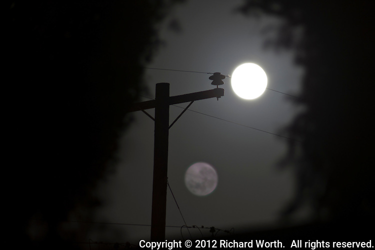 In an unusual twist, the full moon is captured twice in a single frame: a reflection in a lens filter or other lens aberration.  According to the Farmer's Almanac, the July Full Moon is known as the Full Buck Moon, the Full Thunder Moon or the Full Hay Moon.  http://www.farmersalmanac.com/full-moon-names/