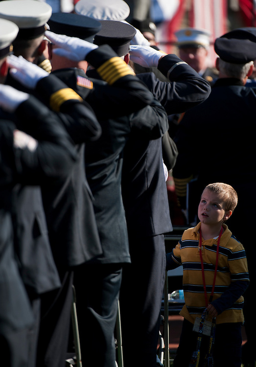 UNITED STATES - OCTOBER 16: Trevor Marshall, son of fallen firefighter Kenneth Marshall Jr., who died unexpectedly at the age of 33 on Thursday, November 25, 2010 in the line of duty while responding to a call for the Rehoboth (Mass.) Fire Department, looks up at firefighters as they salute during the 30th National Fallen Firefighters Memorial at the National Fire Academy in Emmitsburg, Md., on Sunday. Oct. 16, 2011. Rep. Roscoe Bartlett, R-Md., participated in the wreath laying portion of the event. (Photo By Bill Clark/CQ Roll Call)