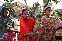 A family stand outside their partially destroyed home. Thousands of people were displaced in Shyamnagar Upazila, Satkhira district after Cyclone Aila struck Bangladesh on 25/05/2009, triggering tidal surges and floods..