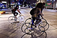 Three young men on bicycles cross a busy intersection at night in downtown Denver, Colorado.
