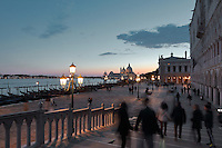 The Riva degli Schiavoni in the evening, with the Doge's Palace or Palazzo Ducale on the right, begun 1340 and built in Venetian Gothic style, and in the distance, the Punta della Dogana with the Basilica di Santa Maria della Salute, designed by Baldassare Longhena in Baroque style, built 1631-87, Venice, Italy. Behind the Doge's Palace is the Biblioteca Nazionale Marciana, or National Library of St Mark's, built in Renaissance style in 1537-53 by Jacopo Sansovino, then extended by Vincenzo Scamozzi in 1588, on the Piazzetta San Marco. The city of Venice is an archipelago of 117 small islands separated by canals and linked by bridges, in the Venetian Lagoon. The historical centre of Venice is listed as a UNESCO World Heritage Site. Picture by Manuel Cohen