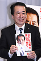 June 17, 2010 - Tokyo, Japan - Japanese Prime Minister Naoto Kan, who is also leader of the ruling Democratic Party of Japan (DPJ), poses for photographers with a copy of his party's pledge next to a campaign poster during a news conference in Tokyo, Japan, on June 17, 2010. Japan's ruling Democratic Party was set to unveil its campaign pledges for elections on July 11, and announced a plan to halve the world's largest public debt in six years.