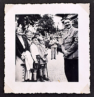 BNPS.co.uk (01202 558833)<br /> Pic: C&amp;TAuctions/BNPS<br /> <br /> Included in its pages is a candid shot of a smiling Hitler surrounded by schoolchildren at the Berghof.<br /> <br /> A photo album containing never-before-seen candid snaps of Adolf Hitler that was found in Eva Braun's bedroom drawer in the Fuhrer's Bunker has sold for more than &pound;41,000.<br /> <br /> The remarkable images show the Nazi dictator and his henchmen in rare lighter moments of the Second World War.<br /> <br /> The album, which was unearthed after 72 years, sparked fervent interest and attracted a phone bid of more than double its estimate of &pound;18,000.<br /> <br /> The hammer price was &pound;34,000, with extra fees pushing the final total to &pound;41,140.<br /> <br /> There is one snap of a grinning Hitler in a 'Chaplinesque' pose and offering a playful salute to the person taking the photo outside his Berghof headquarters. Two more show him smiling in front of a crowd of children saluting him.