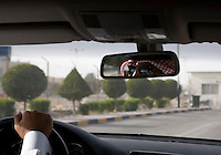 A driver reflected in the rear view mirror as he drives along a road in Doha.