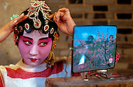 April 15th, 1989, Poyang, Jiangxi Province, China. Member of a traveling opera troupe preparing to perform. Roles in Chinese opera are highly codified. All performers take care of their own make up, clothes and props.