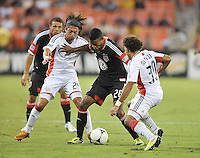 D.C. United forward Lionard Pajoy (26) shields the ball from New England Revolution Lee Nguyen (24) and Kevin Alston (30) D.C. United defeated The New England Revolution 2-1 at RFK Stadium, Saturday September 15, 2012.