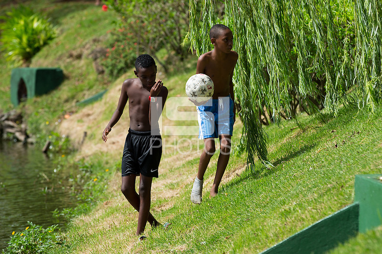 2 kids play with their football