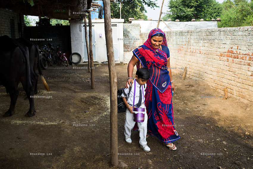 Sugna Jat, 30, walks with her son Hemant Jat, 6, to catch his school bus in Maheshwar, Khargone, Madhya Pradesh, India on 13 November 2014. Hemant, the son of Fairtrade cotton farmers, wants to be a police man when he grows up and gets a 5% discount of school fees at the Vasudha school. His parents would be happy if Hemant took over the farm but if he does well in school, he could look for other careers. Photo by Suzanne Lee for Fairtrade