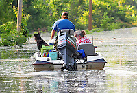 "8/11/11} Vicksburg} -- Vicksburg, MS, U.S.A. -- Patricia Clark hangs her head in despair as her boyfriend Mark Bridges,56, thrift store owner, and his dog ""baby girl""  cruis down Cghicksaw Rd in his bassboat for her first look at her cabin. Mark Bridges and his girlfriend of 12 years Patricia Clark, a homeDepot garden employee, cruise down Chicksaw Rd in a bass boat in North Kings Community in Vicksburg Mississippi Wed. May 5th 2011. This is the firs time for Patricia to try and remove things from her trailer, that is built on 9ft stilts  AND THE WATER IS CURRENTLY AT 15 ft. and rising and is less than 12 inches from being flooded. Mark and Patricia have lived their all their lives and will return when the Mississippi River recedes,. ark has been helping his neighbors get their belongings to safety. Vicksburg a riverfront town steeped in war and sacrifice, gets set to battle an age-old companion: the Mississippi River. The city that fell to Ulysses S. Grant and the Union Army after a painful siege in 1863 is marshalling a modern flood-control arsenal to keep the swollen Mississippi from overwhelming its defenses. PHOTO©SUZIALTMAN.COM.Photo by Suzi Altman, Freelance."