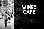 A man waling by wall that says Wing's Cafe, in Gastown