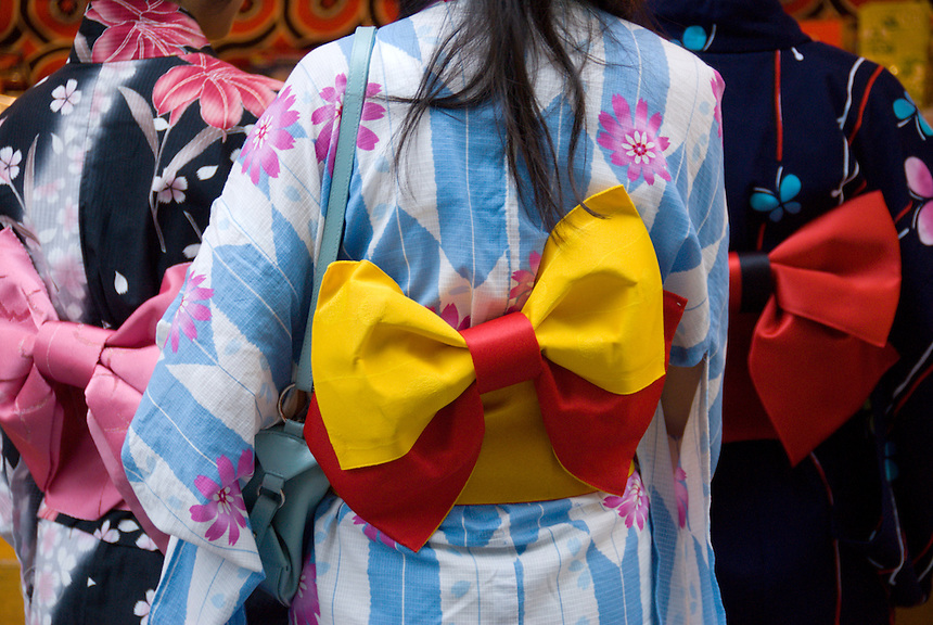 Teenage girls in traditional summer kimono, or yukata, with colourful obi belts at a summer festival, Japan.