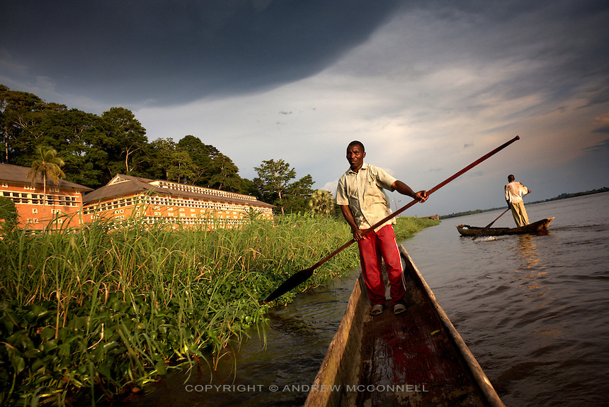 Men navigate their pirogues along the Congo river past the Yangambi Research Station in, Yangambi, DR Congo, on Saturday Dec. 6, 2008. The largest building in Yangambi faces the riverfront and was perviously a maintenance centre and repair garage for the entire facility. It now lies abandoned and derelict. .Yangambi Research Station is the former Belgian headquarters for all major scientific ecological, biological and agricultural research in Africa between the 1930's and 1960. It stretches for 33 km inland from the river and contains 250 residential houses and many research buildings and offices, including a herbarium and library. At it's height approximately 250 scientists and 500 technicians were based here along with 1000 more Belgian workers ranging from doctors to bricklayers. With the families and constant visitors to the station included the total population of would have ranged in the several thousands. Abandonment began in 1960 with independence and although Congolese attempted to maintain Yangambi, sometimes in co-operation with the Belgians, the facility began to fall into disrepair through the 70's and 80's. War in the 1990's halted all potential for progress and for the past decade a skeleton crew has made a futile attempt to stave off further decline.