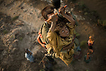 A Pakistan Army helicopter rescue team member evacuates a child trapped on a small piece of land - Dazed, confused, straved and exhausted, the family was rescued from the flood affected areas around the town of Gothki after surviving nearly five days without food and water and exposed to the elements. Many hundreds were trapped by the floods unable to leave because of the speed of the flooding or because they had no means to arrange an escape.