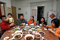 De gauche à droite : Li Fang, Li Siqi, Li Daquan, Qiang Yun, Gao Cuilan, et Li Quanxia partagent le repas du samedi soir dans leur appartement, à Baoshan, près de Shanghai, le 10 mai 2008. En Chine, les femmes conservent leur nom de jeune fille à vie, même lorsqu'elles se marient, et le nom de famille précède toujours le prénom. Les Li vivent à trois générations sous le même toit, pour pouvoir « s'entraider » à Shanghai, où ils sont arrivés il y a cinq ans. Photo par Lucas Schifres/Pictobank