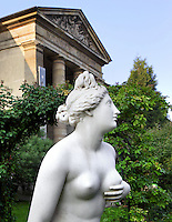 Low angle mid-length view of the statue called Venus genitrix or Venus animant l'univers, created by Louis-Charles Dupaty in 1810 and located in the Rose Garden of the Jardin des Plantes, Paris, 5th arrondissement, France. In the background can be seen the Galerie de Mineralogie, de Geologie et de Paleobotanique (Gallery of Minerology, Geology and Paleobotany). Founded in 1626 by Guy de La Brosse, Louis XIII's physician, the Jardin des Plantes, originally known as the Jardin du Roi, opened to the public in 1640. It became the Museum National d'Histoire Naturelle in 1793 during the French Revolution. Venus Genitrix was given to the Museum National d'Histoire Naturelle circa 1818 and was classified as Historical Monuments in 1982.