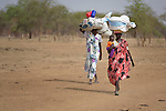 Dinka Ngok women carry their belongings as they accompany cattle herders driving animals southward in the contested Abyei region along the border between Sudan and South Sudan. Fearful of incursions by Misseriya nomads from the north, they and other residents are fleeing south to avoid violent confrontations. Residents of the area also fled south in 2011 after a prolonged attack by soldiers and militias from the northern Republic of Sudan. Although the 2005 Comprehensive Peace Agreement called for residents of Abyei--which sits on the border between Sudan and South Sudan--to hold a referendum on whether they wanted to align with the north or the newly independent South Sudan, the government in Khartoum and the northern-backed Misseriya, excluded from voting as they only live part of the year in Abyei, blocked the vote and attacked the majority Dinka Ngok population. The African Union has proposed a new peace plan, including a referendum to be held in October 2013, but it has been rejected by the Misseriya and Khartoum. The Catholic parish of Abyei, with support from Caritas South Sudan and other international church partners, has maintained its pastoral presence among the displaced and assisted them with food, shelter, and other relief supplies.