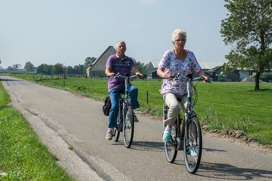 Nederland, Zaanstad, 4 sept 2014<br /> Landschap met ouderen op de fiets net buiten Wormerveer. <br /> <br /> Foto: (c) Michiel Wijnbergh