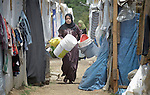 A woman walks between tents in a settlement of Syrian refugees in Minyara, a village in the Akkar district of northern Lebanon. Lebanon hosts some 1.5 million refugees from Syria, yet allows no large camps to be established. So refugees have moved into poor neighborhoods or established small informal settlements in border areas. International Orthodox Christian Charities, a member of the ACT Alliance, provides a variety of support for families in this settlement.