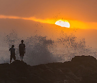 Two surfers look out at big winter waves breaking in Waimea Bay and a brilliant sunset as a wave pounds the rocky shoreline, North Shore, O'ahu.