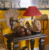 A collection of African masks on a sidetable in the living room