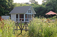 A bespoke summer house of painted tongue-and-groove is situated on the lawn amongst meadow flowers