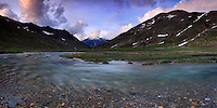 A panoramic view of Pian del Nivolet, the Savara river and the Grivola in the background at sunset. Pian del Nivolet is an awesome plateau at more than 2600 meters of altitude in the heart of the Gran Paradiso National Park, the largest and oldest protected area of Italy. This is stitched from 8 vertical frames.