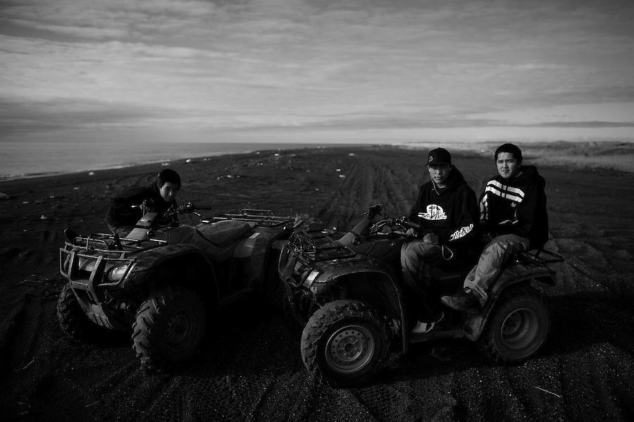 Three teen-age Native Alaskan Inupiaq boys sit on ATV's on the beach near the Alaskan Chuchki Sea barrier island town of Kivalina on Thursday Sept. 20, 2007.  The town, which has already been evacuated once this year, is facing permanent abandonment as successive fall storms in recent years have caused serious erosion to the villages' waterfront threatening the community's homes, fuel farm, and landing strip. The effect of the storms, which have struck the area for millenia, has become ever more grave as the sea ice which once shielded the island appears later each year as the result of warming temperatures. The village's residents are split over whether the abandonment should take place or whether the community should remain at all costs. Seeing greater opportunities and attractions in larger towns further south, many of the village's youth favor abandonment.