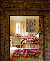 The entrance to the bedroom is surrounded by a hand-carved Indian door frame